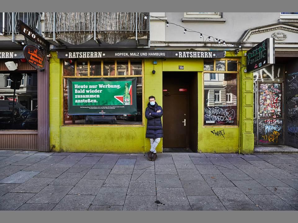 """Bild: Inhaber Martin Konkel vor seiner geschlossenen Bar Parzelle mit einer Werbebotschaft der Marke Heineken. Mit der kreativen """"Shutters"""" Plakatkampagne unterstützt Heineken im Lockdown seine Partner aus der Gastro- und Barszene. Die Buchung der Werbeflächen an Fassaden, Fenstern und Rollläden der Lokalitäten kommt direkt den Besitzern zugute. (Bildrechte: Heineken   Fotograf: Julia Schwendner)"""